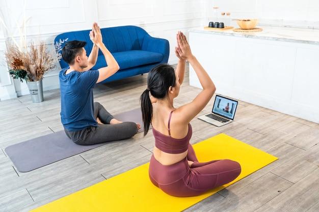 Giovane coppia sportiva asiatica che guarda dal vivo o video tutorial pratica lezione di yoga a casa