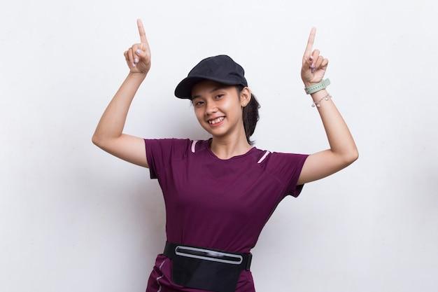 Giovane donna sportiva asiatica che indica dito su spazio vuoto su fondo bianco