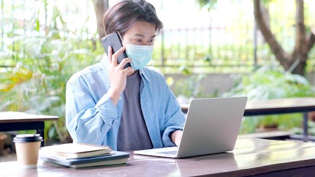 Giovane studente asiatico che indossa una maschera di protezione che parla al telefono cellulare