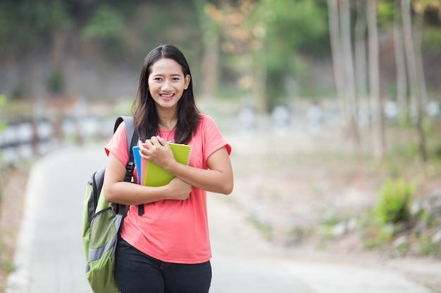 Giovane studentessa asiatica all'aperto, posando dolcemente verso la telecamera