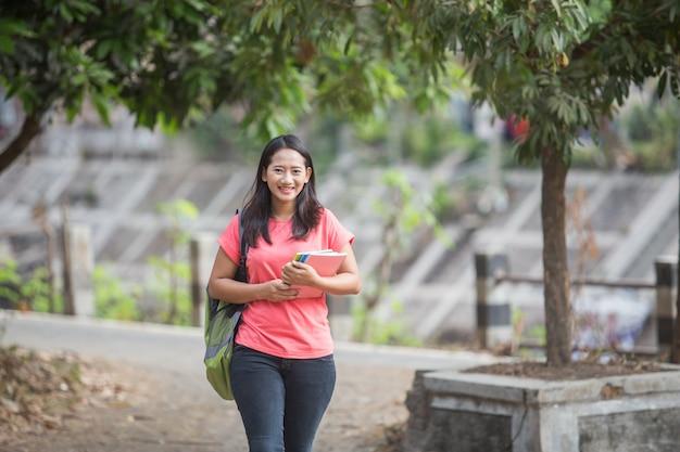 Camminata all'aperto del giovane studente asiatico mentre tenendo il suo libro