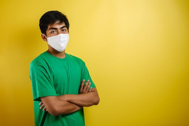 Un giovane studente asiatico che indossa una maschera medica che protegge dalla diffusione della malattia da virus corona. primo piano di un uomo con una maschera chirurgica sul viso su sfondo giallo