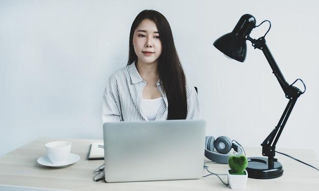 I giovani insegnanti asiatici insegnano divertendosi online dal loro ufficio a casa