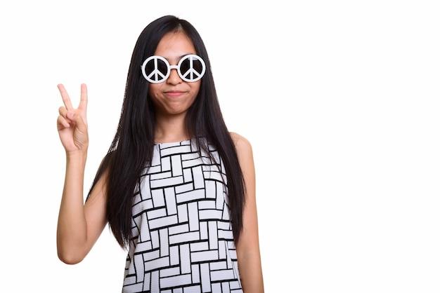 Giovane adolescente asiatico che dà segno di pace mentre indossa gli occhiali da sole