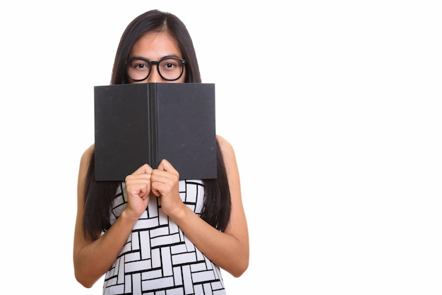 Giovane ragazza adolescente asiatica del nerd che si nasconde dietro il libro