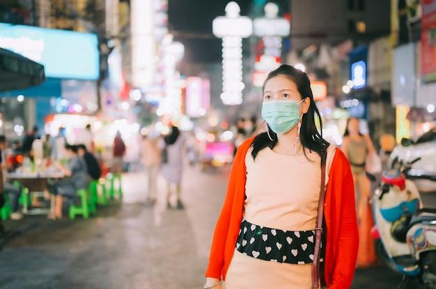 Giovane turista asiatico donna che indossa una maschera per la protezione dall'epidemia di virus corona a chinatown di notte