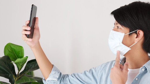 Giovane studente universitario asiatico che tiene il telefono cellulare e fa videochiamate mentre indossa la maschera di protezione al campus, distanza sociale, covid 19