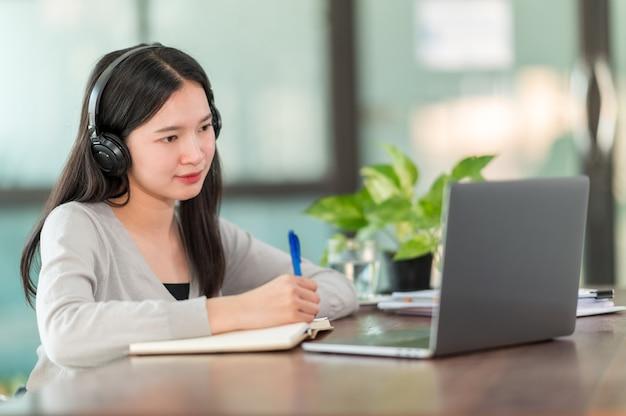 Una giovane studentessa universitaria asiatica che indossava le cuffie per studiare online a casa, durante il periodo dell'epidemia di virus e non frequentava l'università.