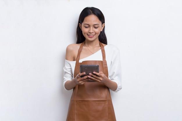 Giovane donna asiatica barista o cameriera utilizzando smartphone mobile isolato su sfondo bianco