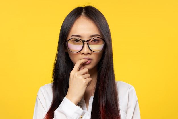 La giovane donna asiatica su una posa blu dello spazio, emozioni differenti, deride su
