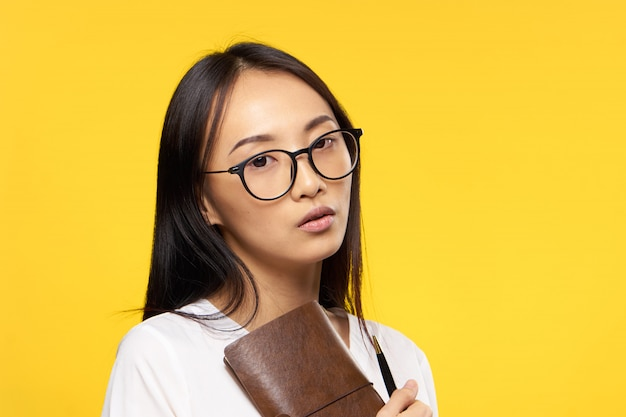 La giovane donna asiatica su una parete blu che posa, le emozioni differenti, deride su