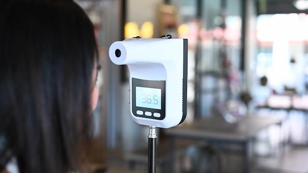 Temperatura corporea della giovane donna asiatica che controlla prima dell'accesso alla costruzione dal termometro a infrarossi sulla fronte