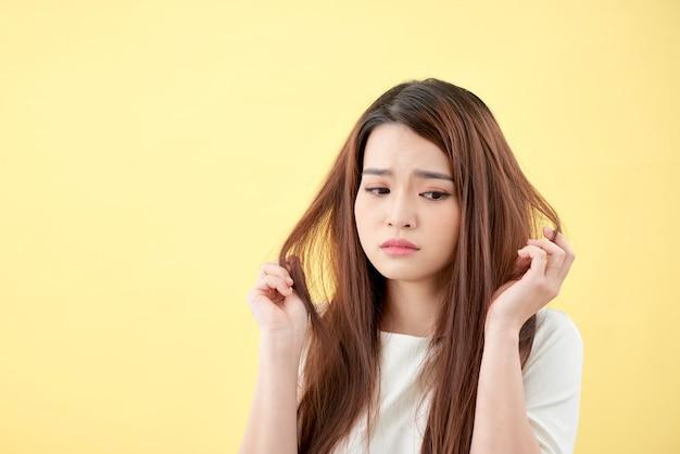 Giovane donna asiatica che si spazzola i capelli e deludente si condiziona i capelli