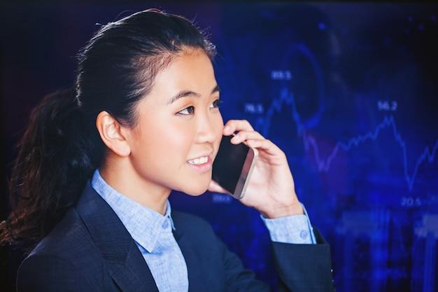 Giovane donna asiatica che chiama il telefono davanti ai grafici della borsa valori
