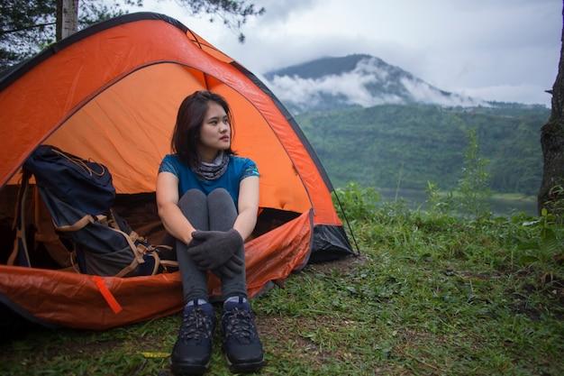 Giovane donna asiatica in campeggio o picnic nel lago della foresta.