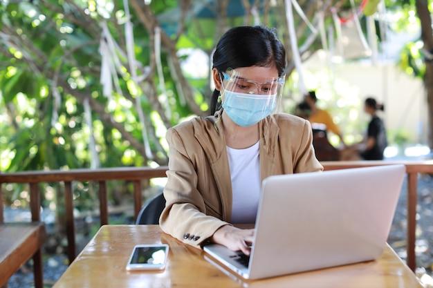 Giovane donna asiatica in abito casual con visiera e maschera protettiva per l'assistenza sanitaria