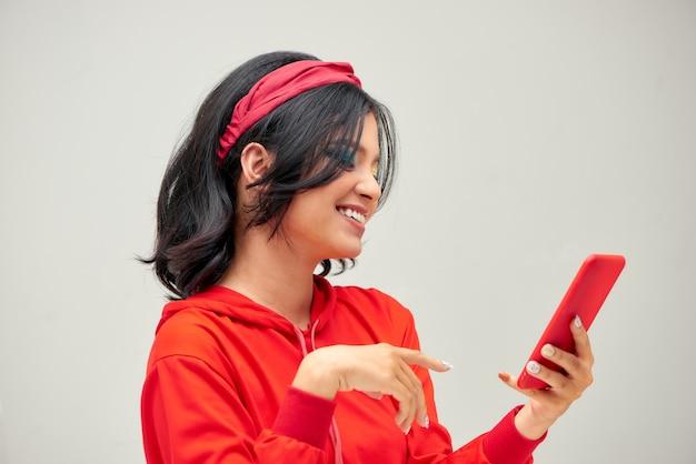 Giovane donna asiatica in chat e navigazione in internet sul telefono cellulare su copia spazio isolato su uno sfondo grigio
