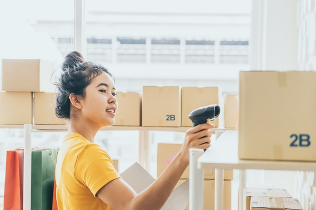 Giovane donna asiatica che controlla le merci sullo scaffale di riserva al magazzino
