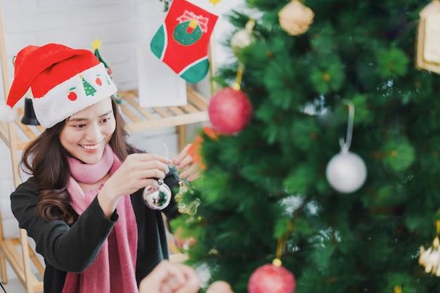 Giovane donna asiatica che decora un albero di natale