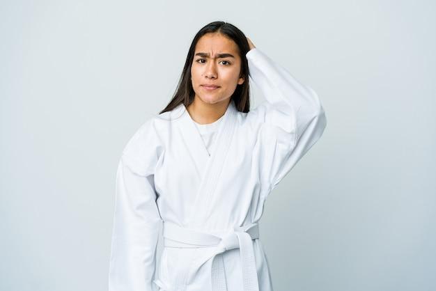 Giovane donna asiatica che fa karate isolato sul muro bianco essendo scioccata, ha ricordato un incontro importante