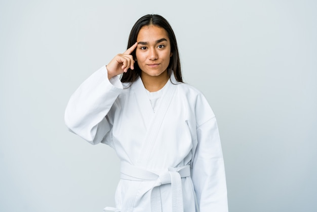 Giovane donna asiatica che fa karate isolato sul tempio di puntamento muro bianco con il dito, pensando, concentrato su un compito