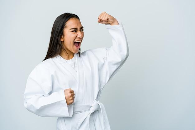 Giovane donna asiatica che fa karate isolato sul muro bianco alzando il pugno dopo una vittoria, concetto vincitore.