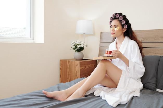Giovane donna asiatica che beve tè e legge un libro quando si riposa sul letto dopo aver fatto un bagno caldo