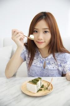 Giovane donna asiatica che mangia alimento dolce della torta del crape del tè verde