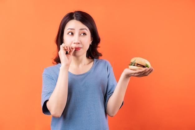 Giovane donna asiatica che mangia hamburger sull'arancia