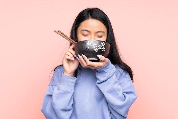 Giovane donna asiatica che mangia le tagliatelle isolate
