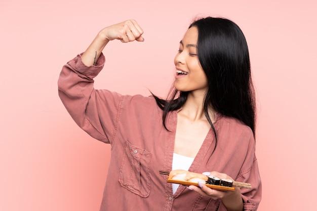 Giovane donna asiatica che mangia i sushi sopra fondo isolato