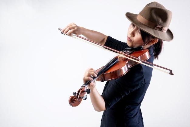 Giovane donna asiatica musicista elegante che suona il violino nella musica classica