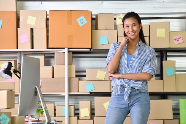 Giovane imprenditore asiatico imprenditore che lavora a casa per lo shopping online e preparazione del prodotto pacchetto