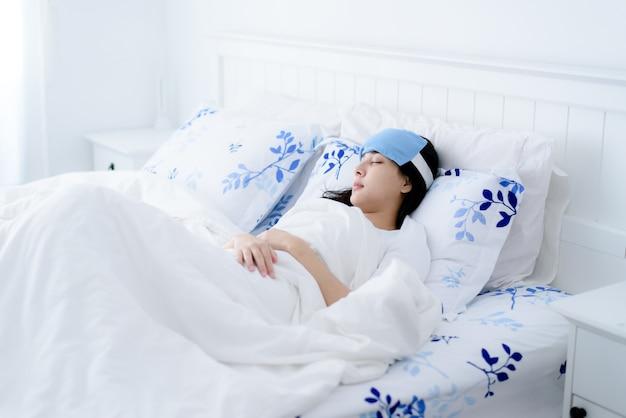 La giovane donna asiatica non si sente bene e usa un cuscinetto fresco per ridurre la temperatura durante il sonno su un letto.