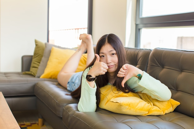 Giovane donna asiatica che si sente confusa, incerta e insicura, valutando il bene e il male in diverse opzioni o scelte