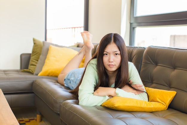Giovane donna asiatica che si sente scontenta e delusa, sembra seria, infastidita e arrabbiata con le braccia incrociate