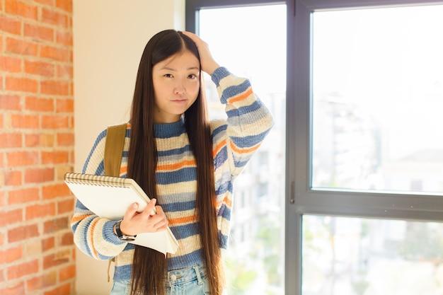 Giovane donna asiatica che si sente frustrata e infastidita, malata e stanca di fallire, stufo di compiti noiosi e noiosi