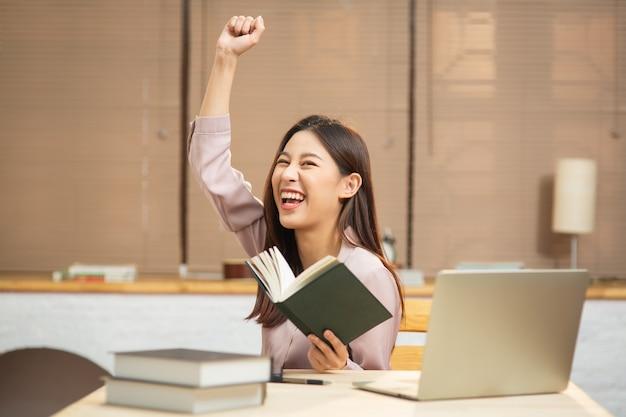 Giovane donna asiatica che si sente felice ed eccitata durante la lettura del libro per avviare una piccola impresa a casa
