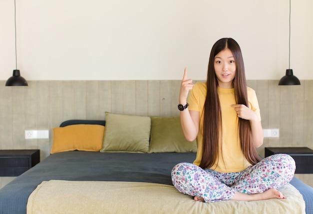 Giovane donna asiatica che si sente orgogliosa e sorpresa, indicando se stessa
