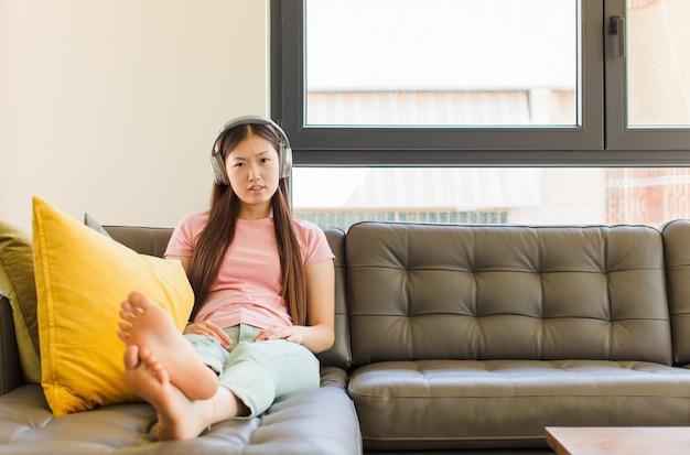 Giovane donna asiatica che si sente perplessa e confusa, con un'espressione stupida e sbalordita guardando qualcosa di inaspettato