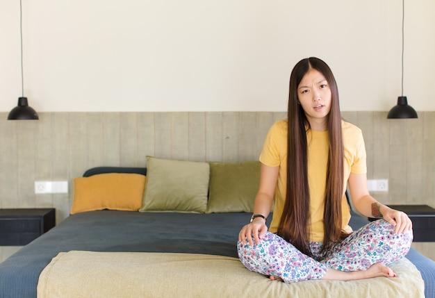 Giovane donna asiatica che si sente perplessa e confusa, con un'espressione stupita e sbalordita guardando qualcosa di inaspettato