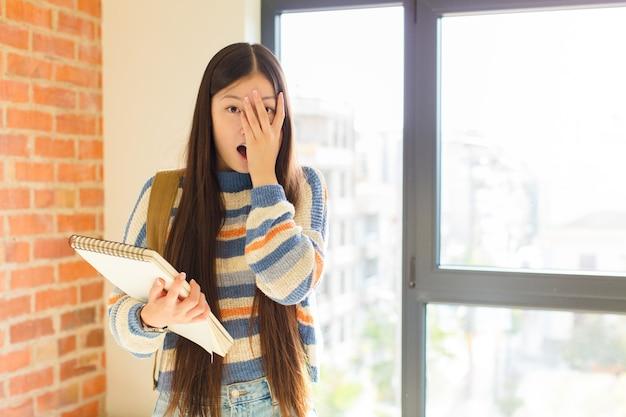 Giovane donna asiatica che si sente spaventata o imbarazzata, sbirciare o spiare con gli occhi semicoperti dalle mani