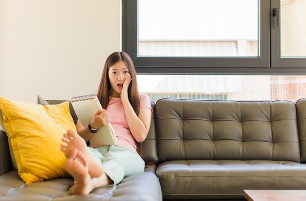Giovane donna asiatica che si sente scioccata e spaventata, sembra terrorizzata con la bocca aperta e le mani sulle guance
