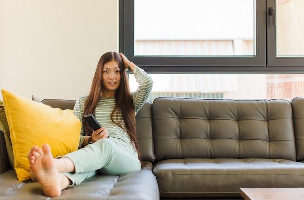 Giovane donna asiatica che si sente stressata, preoccupata, ansiosa o spaventata, con le mani sulla testa, in preda al panico per errore