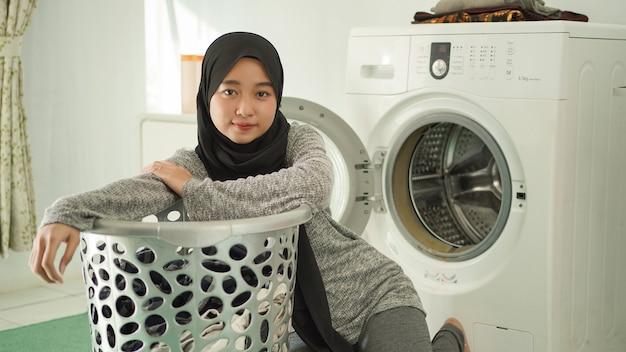 Giovane donna asiatica che si prepara a fare il bucato a casa