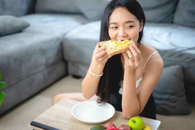 Giovane donna asiatica ragazza che tiene cibo salutare verdura fresca nello stile di vita a casa, donna bella persona vegetariana che fa nutrimento dietetico mangia insalata, la gente sorride felice, concetto di cibo sano