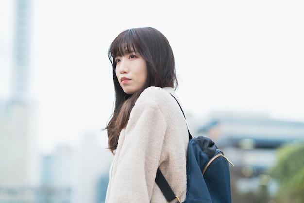 Giovane donna asiatica che esce con uno zaino sulla schiena