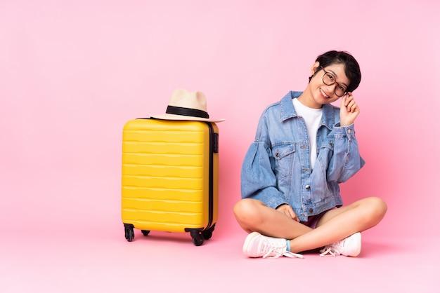 Giovane donna asiatica che va viaggiare sopra fondo isolato