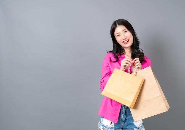 Giovane donna asiatica felice sorridente e gioiosa holding borse della spesa in camicia rosa