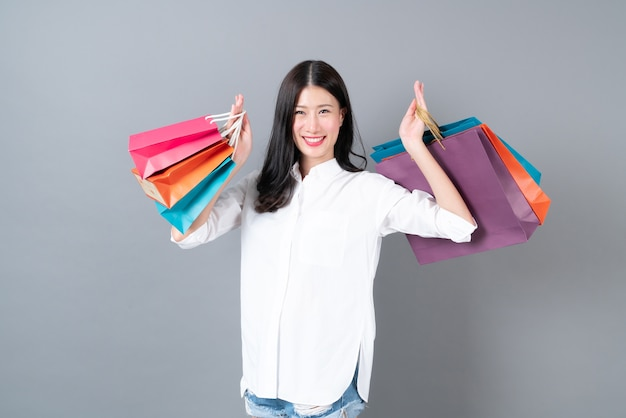 Giovane donna asiatica felice sorridente e gioiosa holding borse della spesa in camicia bianca